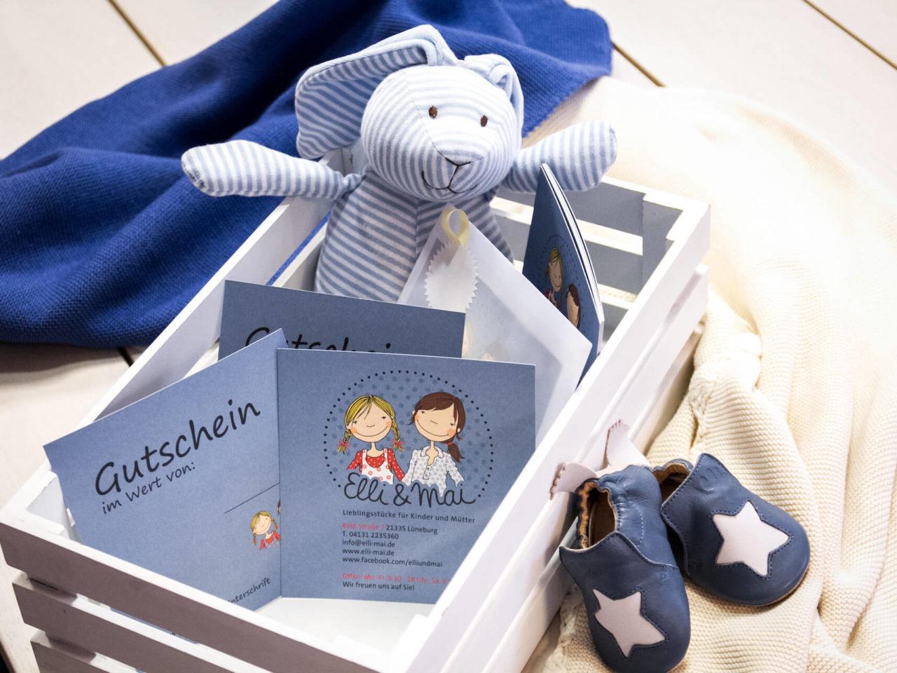 Wunderschöne Gutschein mit dem Elli & Mai Logo in einer Holzkiste mit einem Paar Babyschuchen und einem Kuscheltier