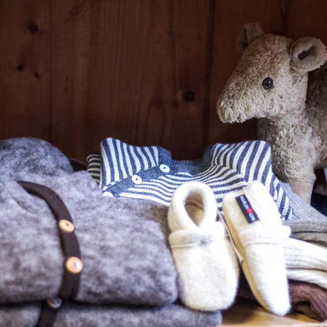 Regal bei Elli und Mai mit einem Body aus Wolle-Seide, einem Kuscheltier aus biologisch angebauter Baumwolle und Hausschuhen von Living Kitzbühel