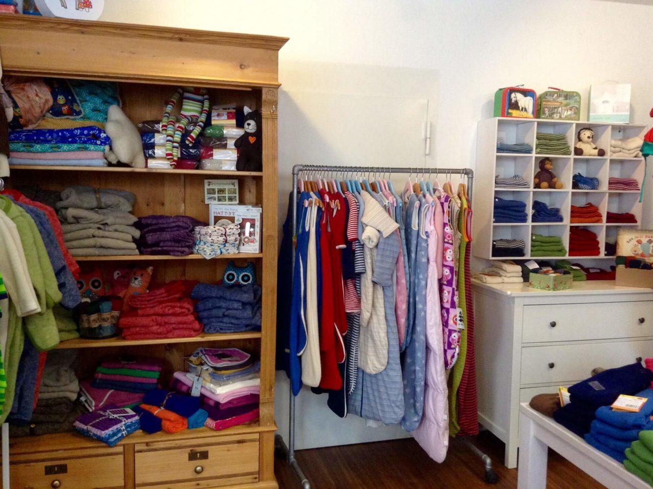 Im Fachgeschäft Elli und Mai sieht man Regale und Kleiderstanden voller bunter Kindermode sowie Still- und Schwangerenmode