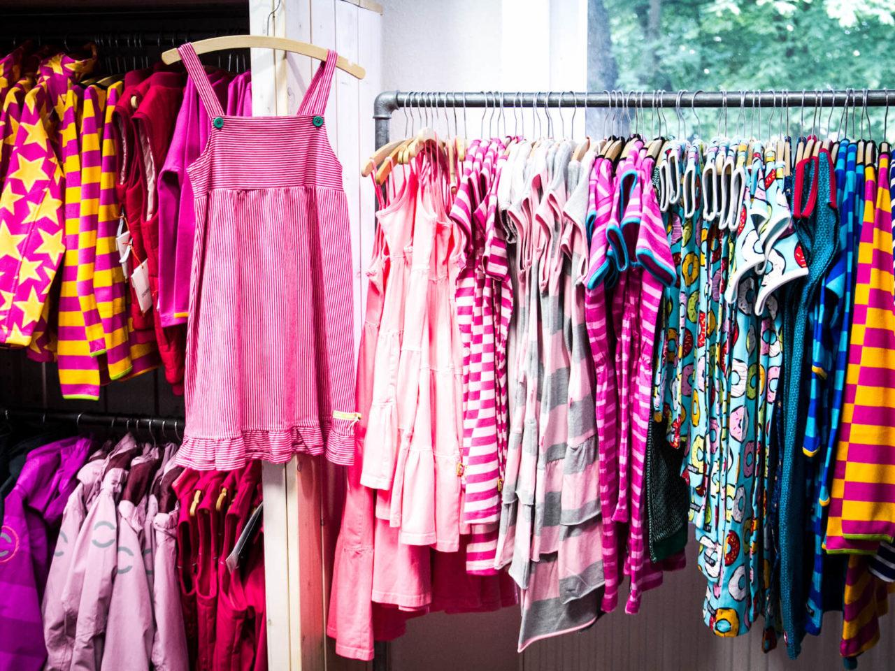 Fröhlich, bunte Mädchenkleider in pink, rosa, gelb und anderen Farben hängen an einer Stange im Elli & Mai in Lüneburg