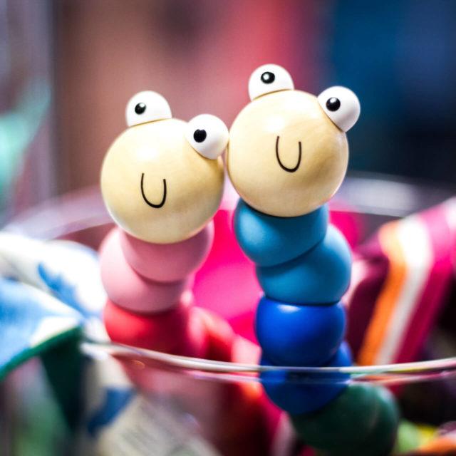 Ein blauer und ein rosaner Kuscheltiere in Form eines Wurmes im Geschäft für Kindermode