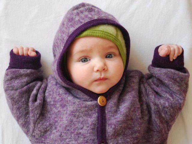 Ein Baby mit grüner Mütze und lila Strampelanzug zu Besuch bei Elli und Mai Kindermode