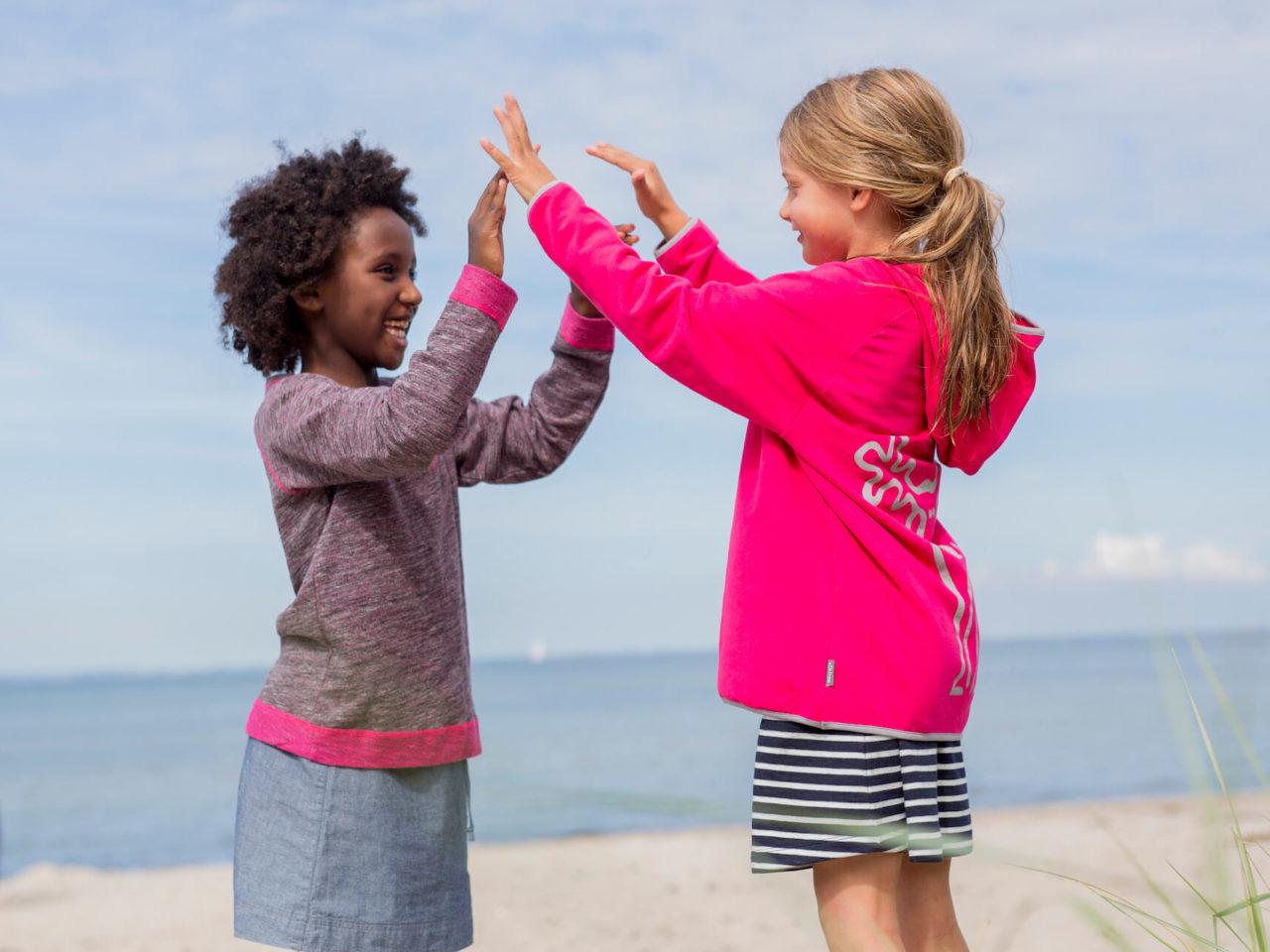 Zwei Mädchen in bunten Pullovern und Softshelljacken von Elli und Mai spielen am Strand