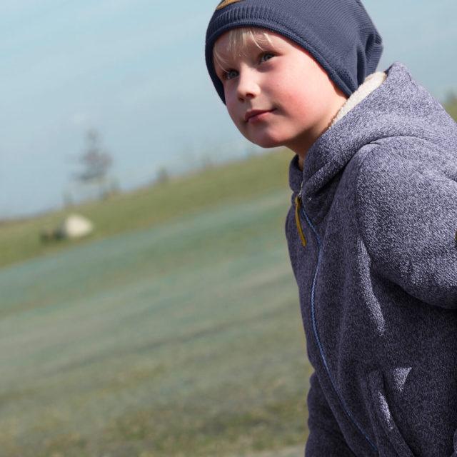 Ein blonder Junge mit warmer Kinderkleidung von Elli und Mai spielt auf einer Wiese