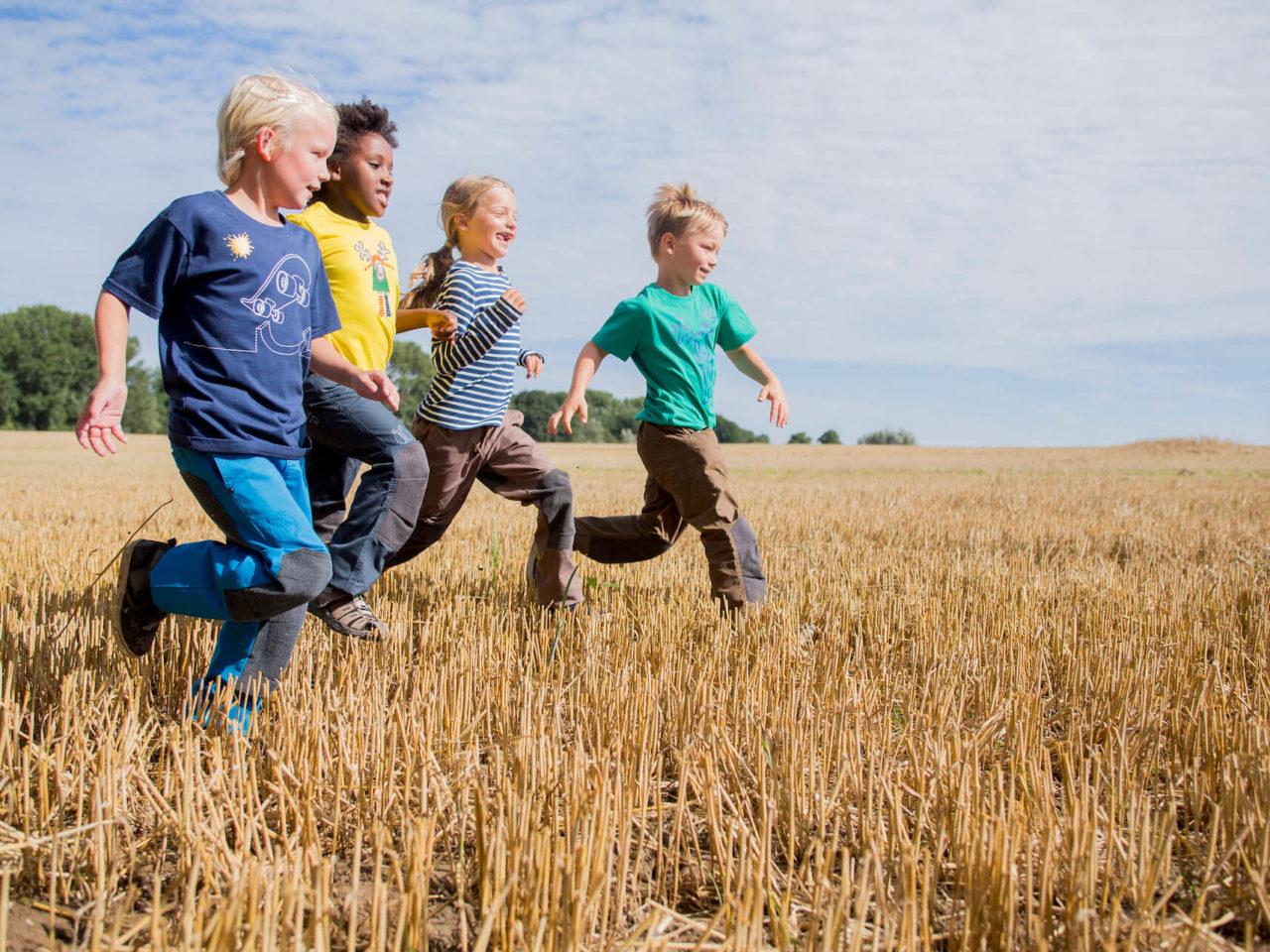 Drei Jungs und ein Mädchen in bunter Kindermode von Elli & Mai laufen üebr ein Feld